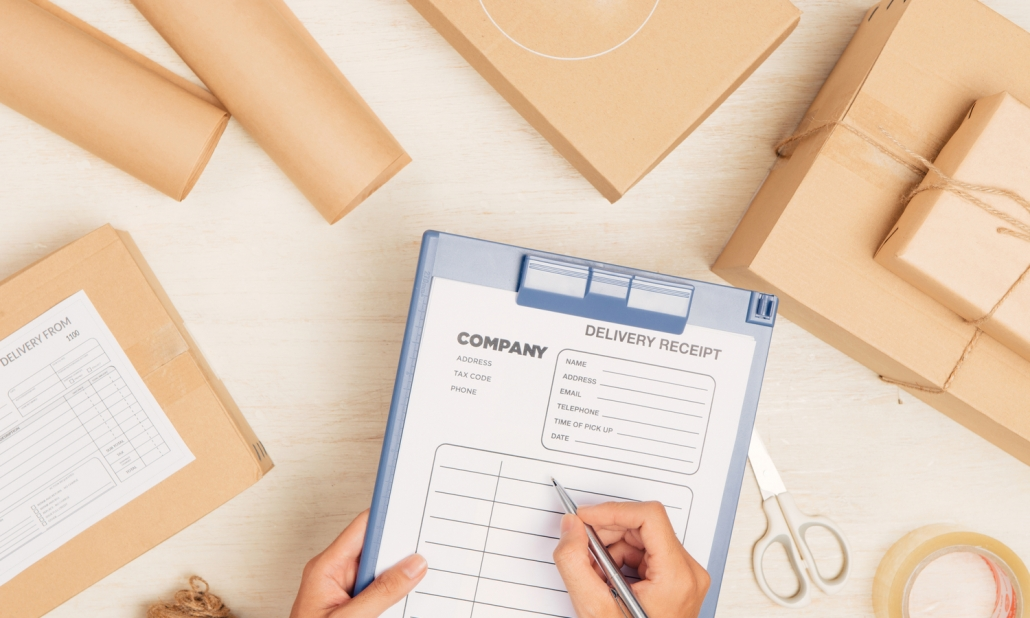 Courier making notes in delivery note among parcels at table